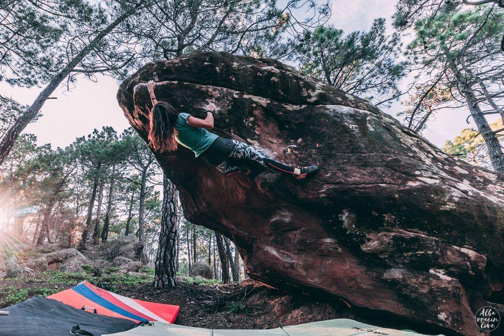 Fotografía de una mujer escalando bulder en otoño
